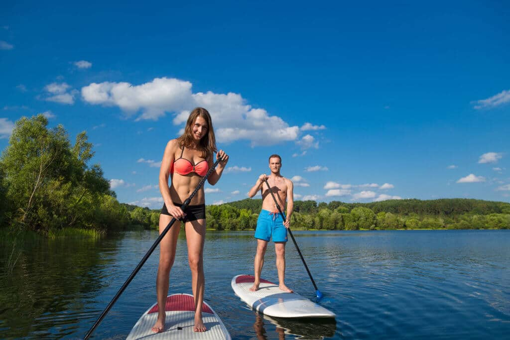 Young couple SUP paddleboarding on lake at Wilderness Presidential Resort