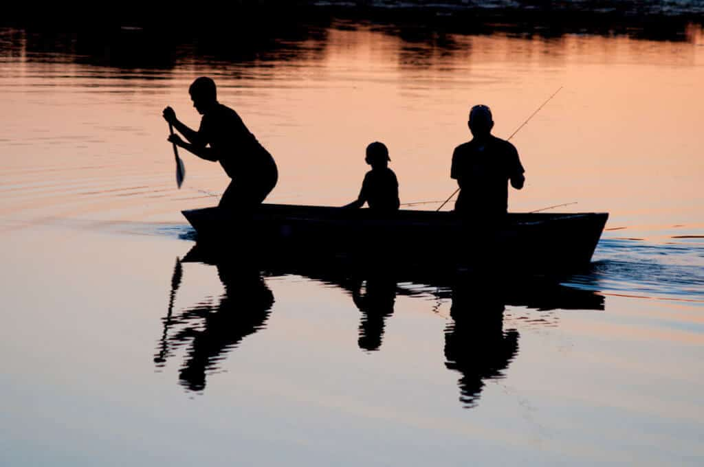 Kids fishing with parent at dusk stock image