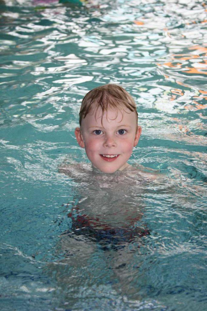 Kid swimming in indoor pool