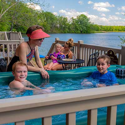 Children in hot tub with Mom and family in background with view of lake.