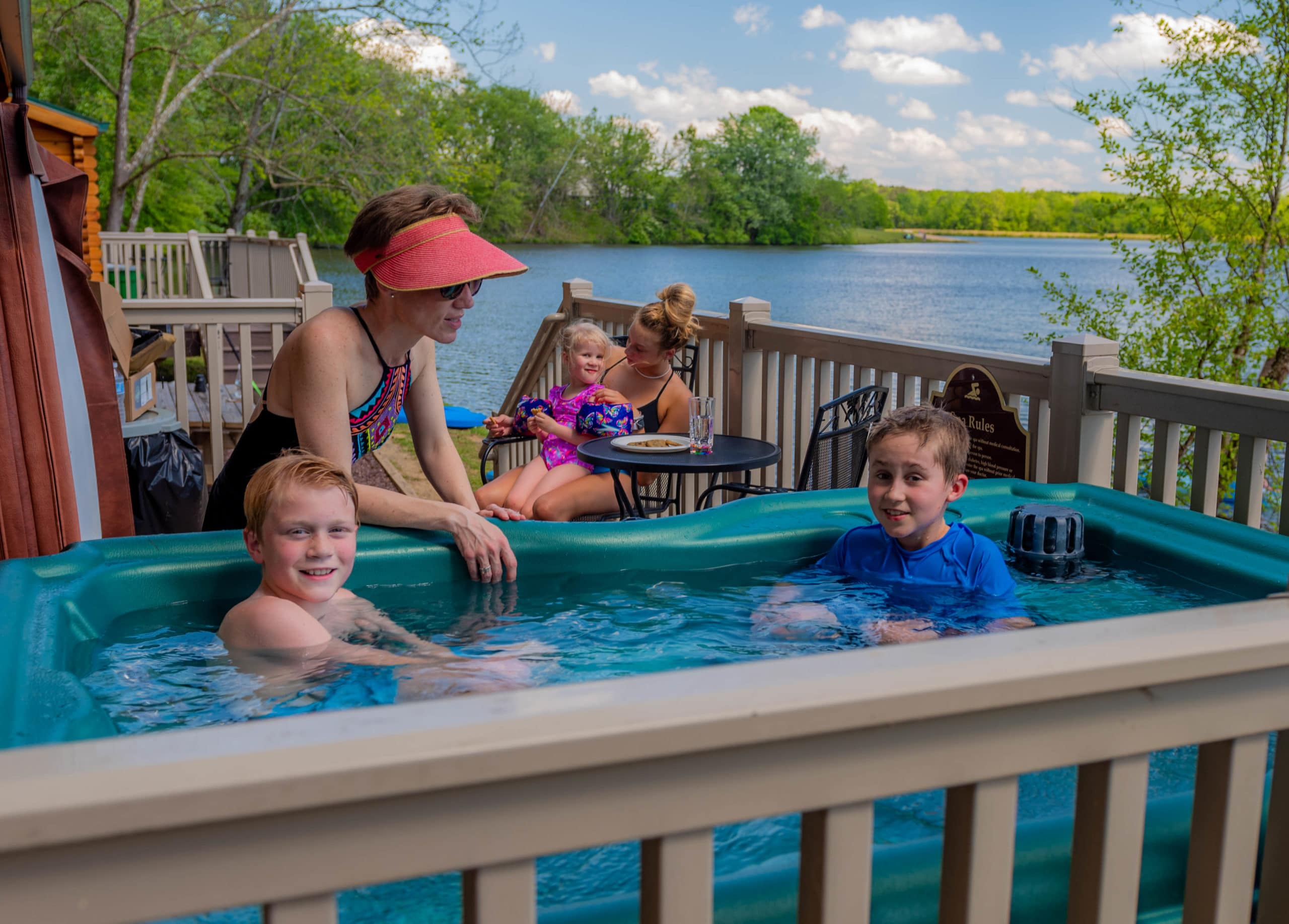 Boys in hot tub on camp cottage deck with Mom and family in background