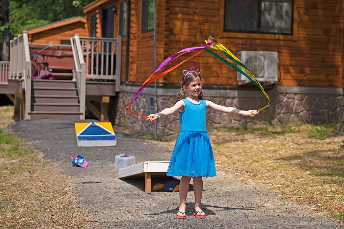 Little girl playing outside a Wilderness Presidential Resort camp cottage