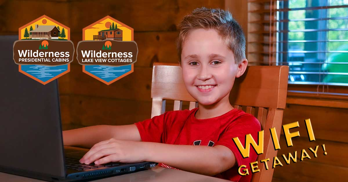 Boy using laptop for virtual school in log cabin