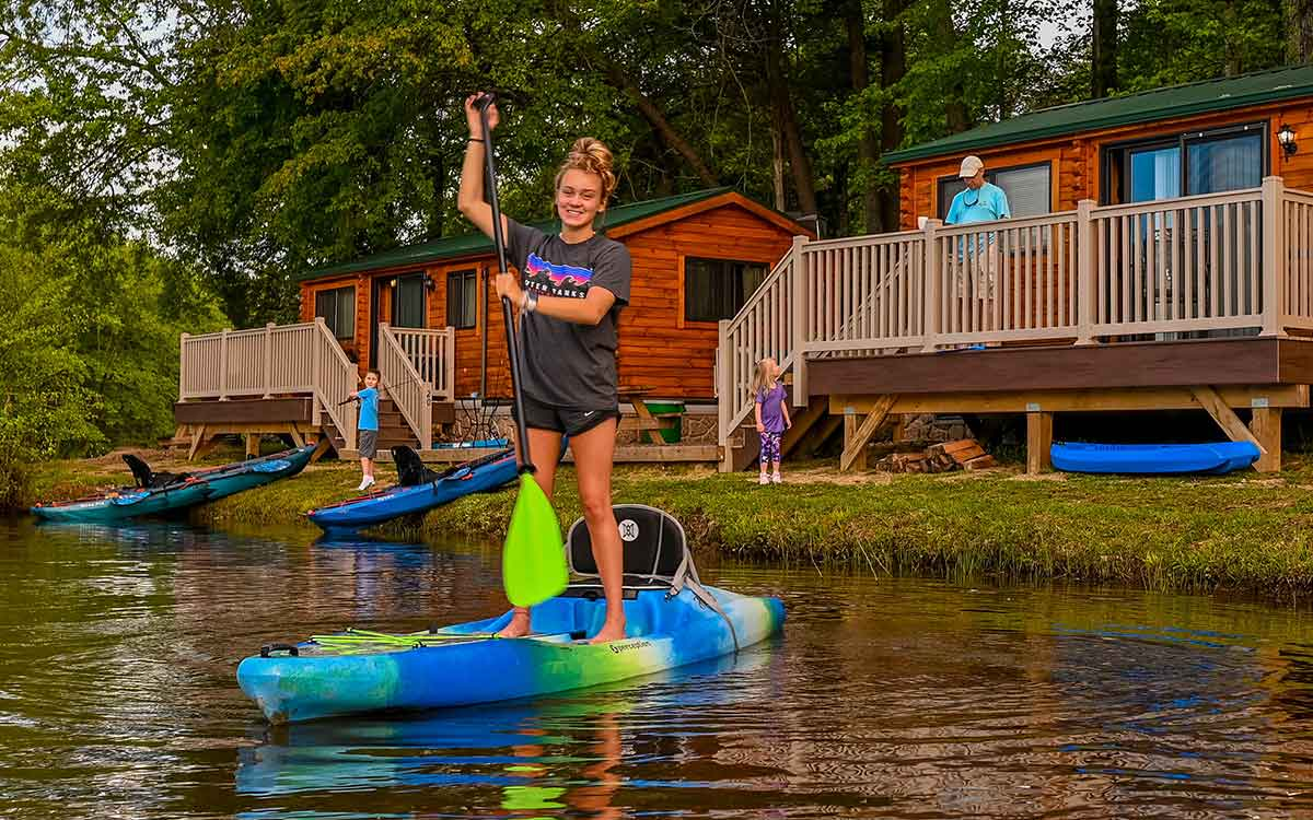 camp rental cabin on cool springs lake with girl on sup and family in background