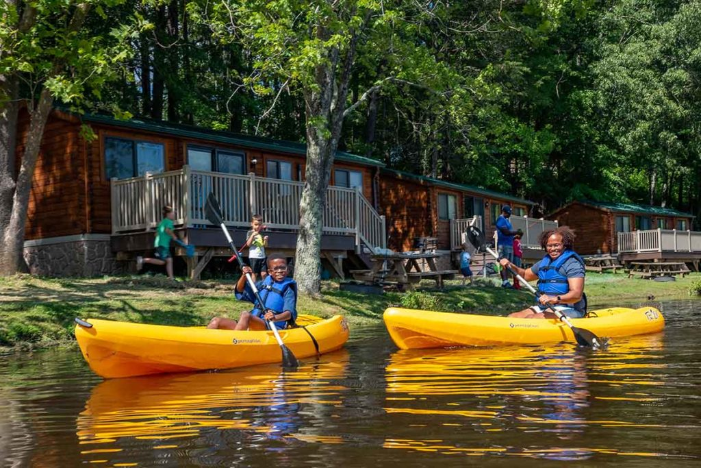 MOther and son paddling kayaks in front of lakeside camp cabins on cool springs lake at WIlderness Presidential resort in fredericksburg virginia