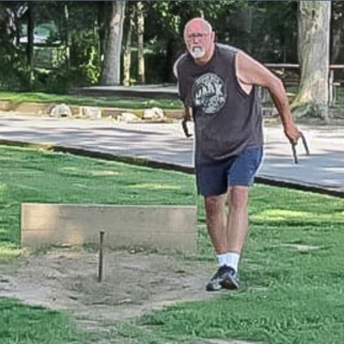 Man playing horseshoes at Americamps RV Resort